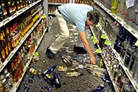 Мужчина, стеллажи, разбитые бутылки
